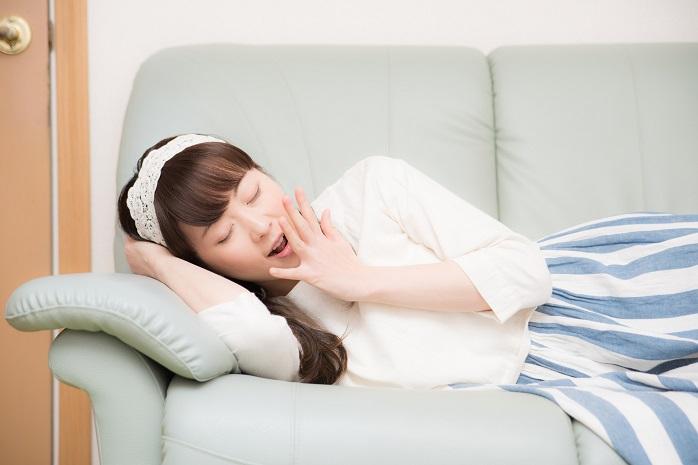 ソファであくびをしている女性