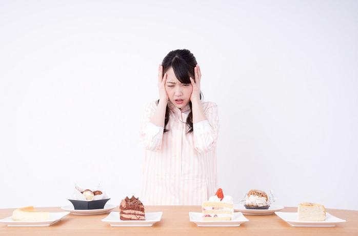 ダイエット中の甘いものを我慢する女性