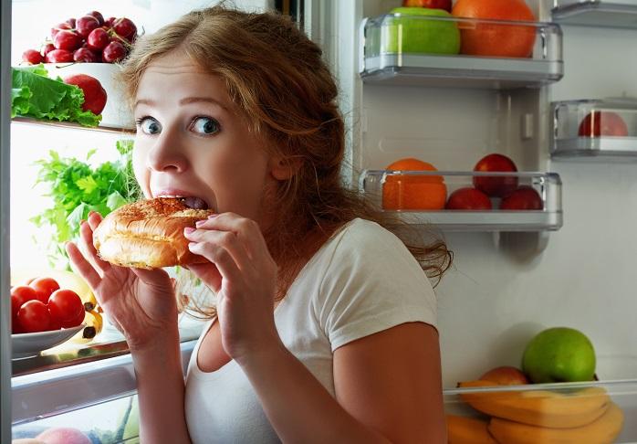 冷蔵庫の前で夜食を食べる女性